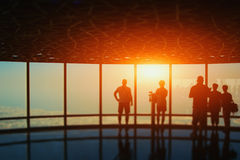 Silhouettes of group of people near the window of skyscraper Stock Image