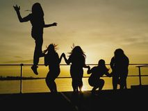 Silhouettes of a group of playful people at sunset. Jumping and enjoying the freedom of the night on a deck overlooking the ocean Stock Images