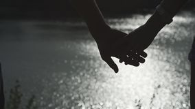 Silhouettes of happy couple hands holding together with river water surface at background