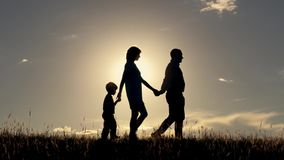 Silhouettes of happy family go holding hands on sunset background.