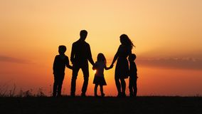 Silhouettes of happy family holding the hands in the meadow during sunset. Happy family enjoying life together. Happy young family spending time together stock video footage