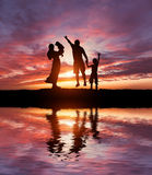 Silhouettes of happy family. Silhouettes of happy parents having good time with their little children on the seacoast royalty free stock images