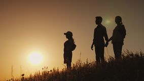 Silhouettes of a happy family, together they meet the dawn in a picturesque place.  Stock Image