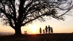 Silhouettes of happy family walking in the meadow near a big tree during sunset. Royalty Free Stock Photo