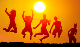 Silhouettes of happy teenagers jumping high. In the air on sunny summer day royalty free stock photo