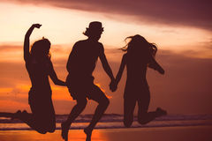 Silhouettes of happy young friends jumping on the Stock Photos
