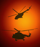 Silhouettes of helicopters during the sunset Stock Images