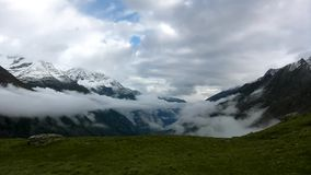 Silhouettes of high Alpine mountains sticking out from heavy mist clouds, deep valleys full of mist stock video footage