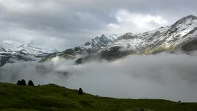 Silhouettes of high Alpine mountains sticking out from heavy mist clouds, deep valleys full of mist stock footage