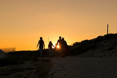 Silhouettes of hikers enjoying sunset. Silhouettes of hikers enjoying sunset view from top of a mountain Stock Photo