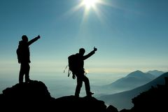 Hikers on mountain top. Silhouettes of hikers showing thumbs up on a mountain top at sunset Royalty Free Stock Photo