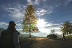 Silhouettes of Hikers and a Swiss Alp Panorama. Swiss Alp silhouettes of hikers and car. An autumnal tree and mountains in the background with a bright glowing Stock Image