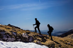 Silhouettes of hikers walking in the mountains Stock Photo