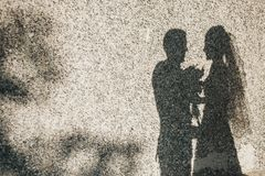 Silhouettes of honeymooners on a wall. Silhouettes of honeymooners in sunlight on a wall texture stone Royalty Free Stock Image