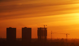 Silhouettes of houses under construction against the sunset Stock Images