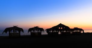 Silhouettes of hovels with the roofs covered with palm leaves for rest on the beach at sunset Stock Image