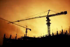 Silhouettes of huge tower cranes stock photos