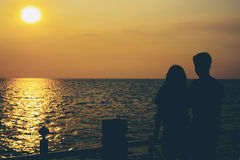 Silhouettes of hugging couple against the sea at sunset. Vintage tone stock images