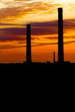 Silhouettes of industrial pipes against the fiery sky Stock Photo