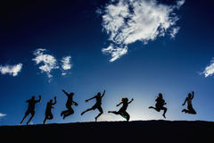 Silhouettes of jumping people. Silhouettes of joyful people jumping against blue sky Stock Photography