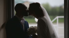 Silhouettes just married couple near big window in rainy day stock footage