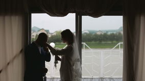 Silhouettes just married couple near big window in rainy day stock video
