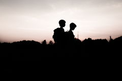 Silhouettes of kids hiking at sunset. Happy boy and girl on summer vacation in mountains. Tourists walking on hill edge carrying backpacks. Summertime fun stock images