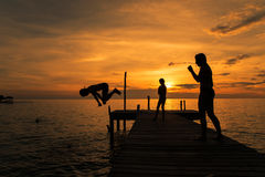 Silhouettes of kids jump into sea from pier.  stock image