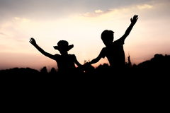 Silhouettes of kids jumping off a cliff at sunset. Boy and girl jump high holding hands. Brother and sister having fun in summer. Friendship, freedom concept Stock Photo