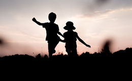 Silhouettes of kids jumping off a hill at sunset. Little boy and girl jump raising hands up high. Brother and sister having fun in summer. Friendship, freedom royalty free stock photo