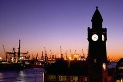 Silhouette of the Landungsbruecken clock tower in Hamburg. Silhouettes of the Landungsbruecken clock tower and container gantry cranes in the harbour of Hamburg Stock Image