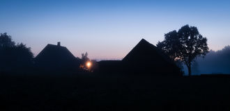 Silhouettes of Latvian farmhouse at sunset Stock Images