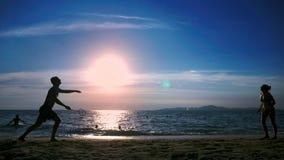 silhouettes les gens jouent au badminton sur la plage au coucher du soleil banque de vidéos