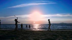 silhouettes les gens jouent au badminton sur la plage au coucher du soleil clips vidéos