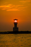 Silhouettes of lighthouse at sunset. Royalty Free Stock Photo