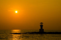 Silhouettes of lighthouse at sunset. Royalty Free Stock Photography