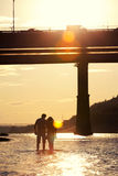Silhouettes of lovers at sunset. Lovers walk at sunset on the river in silhouette Royalty Free Stock Images
