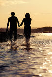 Silhouettes of lovers at sunset. Lovers walk at sunset on the river in silhouette Stock Image
