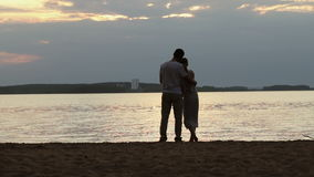 Silhouettes of lovers at sunset. Young beautiful couple embracing on a shore of the lake stock video footage