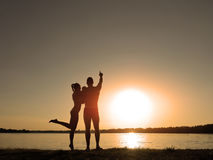 Silhouettes of a loving couple on the beach. Sunset on the beach.  Stock Image