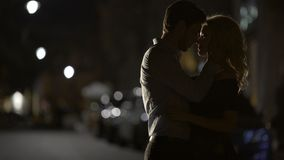 Silhouettes of loving couple embracing each other in the street, relationship