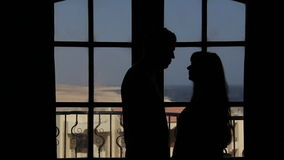 Silhouettes loving couple kissing, background doors, balcony with a sea view stock footage