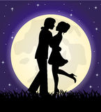 Silhouettes of a loving couple standing in front of the moon Stock Images