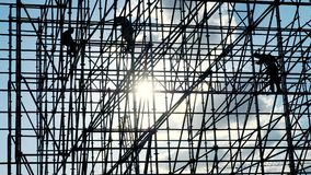 Silhouettes of male engineer worker at construction site. Workers at sunset builders assemble design. Concept building stock footage