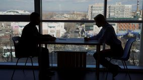 The silhouettes of male and female colleagues are working on the reports at the table. stock video