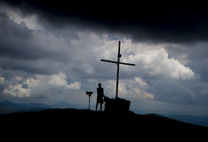 Silhouettes of man and a cross on mountain top Royalty Free Stock Photo