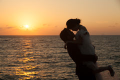 Silhouettes of man lifting girl. Royalty Free Stock Photos
