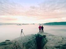 Silhouettes of man photographers. Men on mountain, two men taking photos in autumn morning sunrise Stock Photos