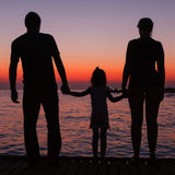 Silhouettes of man, woman and child on the background of the sun Stock Image