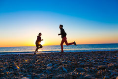 Silhouettes of Man and Woman jogging along Sea Beach at Sunrise Royalty Free Stock Photography